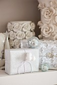 Gifts wrapped in white shimmering paper decorated with small disco balls