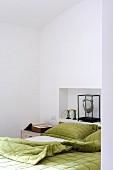 Grüne Bettwäsche neben antiquarischem Buch und Wandnische mit Kunstobjekt am Kopfende