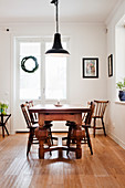 Wooden table with chunky legs and old chairs in bright dining room