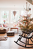 Rocking chair in front of decorated Christmas tree in living room