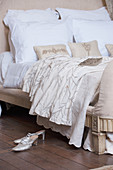 Silver shoes next to Baroque bed with white bedlinen