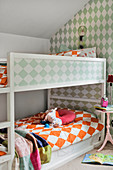 Bunk beds and green and white patterned wallpaper in children's bedroom