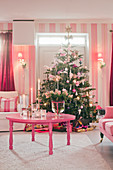 Christmas tree in kitsch living room decorated entirely in pink and hot pink