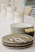 Cutlery and stacked vintage-style plates in front of storage jars on table