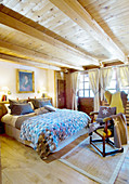 Rustic bedroom with wood-beamed ceiling and lattice windows