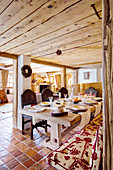 Chunky wooden table and carved wooden chairs on terracotta floor tiles in dining area of chalet