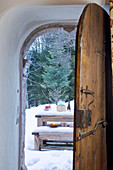 View through rustic, open wooden door to table and benches in snowy landscape