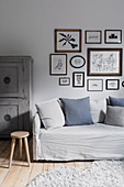 Picture gallery with drawings over the light gray sofa cover