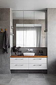 View of washstand with wooden top, above mirror cabinet in the bathroom with gray tiles