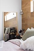 Bett, Nachttisch und Spiegel im Schlafzimmer mit Wand aus recyceltem Eichenholz