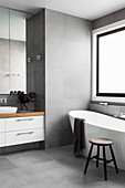 Freestanding bathtub in front of window and vanity in gray tiled bathroom