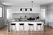 Fitted kitchen with subway tiles, kitchen counter with bar stools and black light in an open living room
