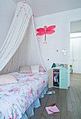 Canopied bed with floral bedlinen in girl's bedroom