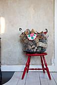 Drahtkorb mit Brennholz auf altem roten Stuhl