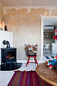 Log burner, basket of firewood on chair and view into kitchen-dining room