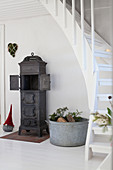 Cast iron stove below winding staircase