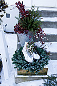 Ice skates on wreath and bucket of branches on steps