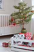 Wrapped presents in white-painted wooden crate in front of small Christmas tree