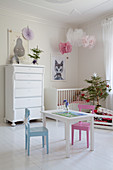 Children's table and chairs and small Christmas tree in white nursery
