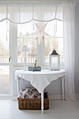 Wintry accessories on console table below window with white curtains