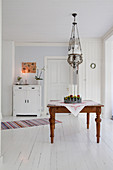 Traditional ceiling lamp above country-house table on white wooden floor