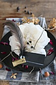 Halloween table decorated with black plate, white paper flower, name tag, black feather and gold clip