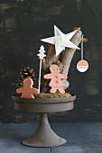 Christmas arrangement of gingerbread men made from clay and paper star on cake stand