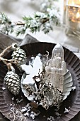 Christmas arrangement of antique glass Father Christmas and silver pine cones in tart tin