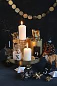 Origineller Adventskranz auf goldener Etagere mit Girlande, Fröbelsternen, Hirschfigur und Geschenken in goldenem Papier vor schwarzem Hintergrund