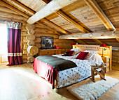 Rustikales Schlafzimmer unter dem Dach eines Blockhauses