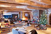 Wohnzimmer mit Weihnachtsbaum und Kerzendeko im Blockhaus