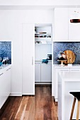 White kitchen with wooden floor and sliding door to the pantry