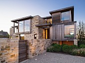 House with complex façade made from stone, wood and glass