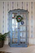 Blue, shabby-chic display case against blue-and-white country-house wallpaper
