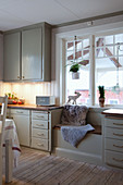 Window seat in rustic kitchen-dining room with winter decorations