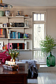 Tall, narrow window next to bookcase in living room with wintry decorations