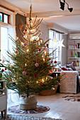 Schlicht geschmückter Weihnachtsbaum im gemütlichen Wohnzimmer