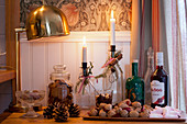 Winter arrangement of candles in bottles, nuts, pine cones and biscuits
