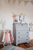 Old grey bureau and clothes rack in child's bedroom
