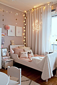 Cosy lighting around bed in girl's bedroom in pastel shades