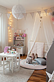 Play kitchen and child's table in child's bedroom with cosy lighting