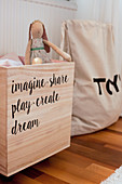 Wooden toy chest with motto made from stickers