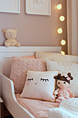 Cushions and doll on child's bed in shades of cream and pink