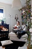 Frau sitzt lesend auf der Recamiere im gemütlichen Wohnzimmer
