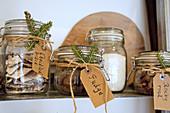 Handwritten labels and fir sprigs on storage jars