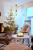 Arrangement of candles on coffee table in front of Christmas tree in cosy living room