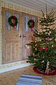 Schlicht dekorierter Weihnachtsbaum vor einem Wandschrank mit zwei Kränzen