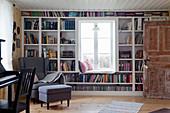 Bücherwand um das Fenster mit Sitzbank im Wohnzimmer