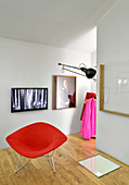 Red designer armchair in front of TV and pictures on wall