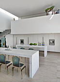 Marble table in front of minimalist kitchen below gallery